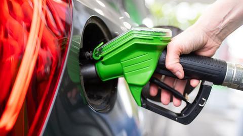 Eine Frau hält an einer Tankstelle an einer Zapfsäule eine Zapfpistole in der Hand und betankt ein Auto. (dpa)