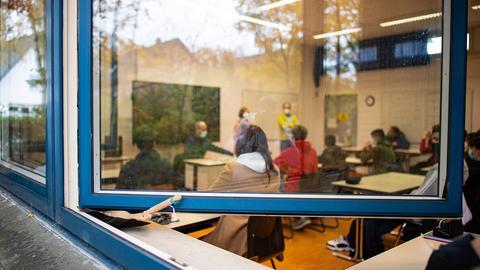 Blick durch das offen stehende Fenster in den Klassenraum einer Schule. (dpa)
