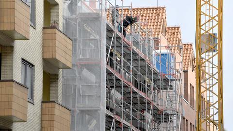 Bauarbeiter stehen in Kiel auf einem Baugerüst an der Baustelle eines Wohn- und Geschäftshauses. (dpa)