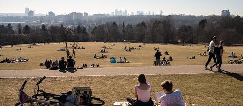 Zahlreiche Menschen lagern auf dem sonnenbeschienenen Lohrberg in Frankfurt am Main mit Blick auf die Skyline der Innenstadt am Horizont. (dpa)