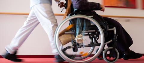 Ein Pfleger eines Pflegeheims schiebt eine Bewohnerin mit einem Rollstuhl. (dpa)