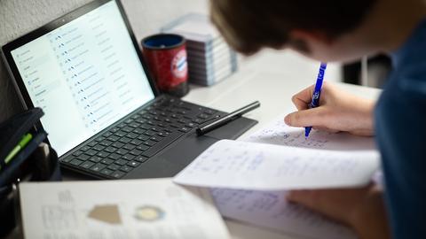 Ein Schüler sitzt in seinem Zimmer am Schreibtisch und erledigt Aufgaben im Rahmen des Homeschooling. (dpa)