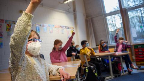 Eine Schülerin einer 4. Klasse hebt im Unterricht an der Grundschule Russee in Kiel die Hand. (dpa)
