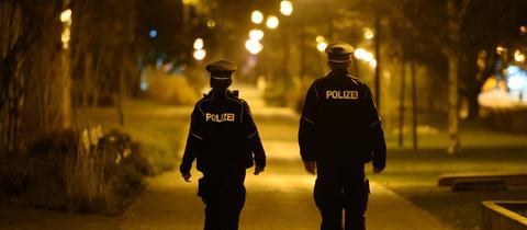 Polizisten laufen in der Nacht im Stadtteil Gorbitz Streife und kontrollieren die Einhaltung der Ausgangssperre. (dpa)