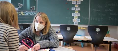 Eine Lehrerin spricht mit einer Schülerin im Unterricht an einer Grundschule (dpa)