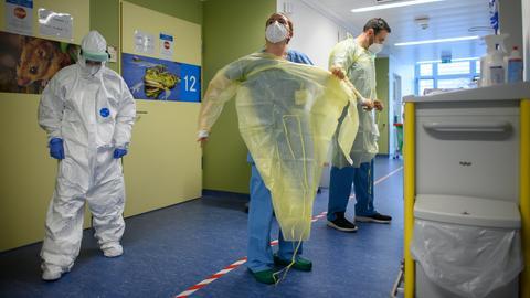 Mitarbeiter ziehen sich auf der Corona-Station in einer Klinik ihre Virenschutzkittel an.  (dpa)