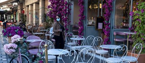 Eine Frau steht vor einem Café in Athen. (AP)