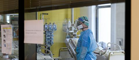 Ein Intensivpfleger ist auf der Covid-19 Intensivstation im Städtischen Klinikum Dresden mit der Versorgung von Corona-Patienten beschäftigt. (dpa)