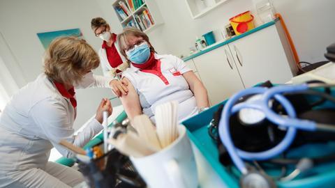 Eine Mitarbeiterin des Gesundheitswesens impft eine Krankenschwester in einer Arztpraxis mit dem Corona-Impfstoff von AstraZeneca. (dpa)