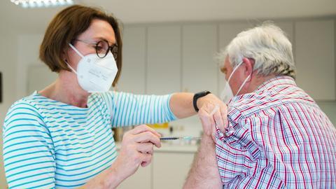 Die Hausärztin Birgitt Lucas verabreicht einem Patienten die erste Impfung gegen Covid-19. Stadt und Landkreis Hof (Bayern) möchten im Rahmen eines Pilotprojektes Corona-Impfungen durch Hausarztpraxen erproben.  (dpa)