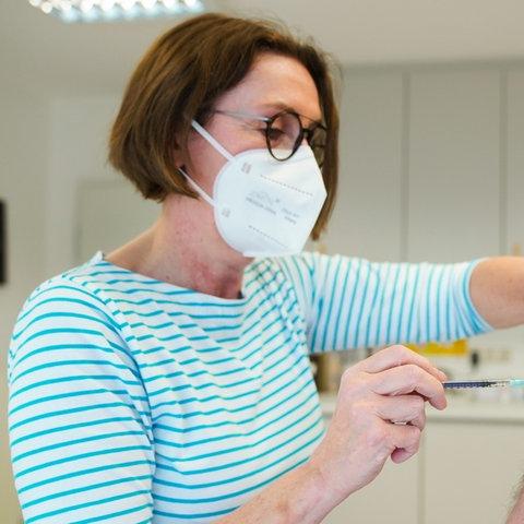 Eine Hausärztin verabreicht einem Patienten die erste Impfung gegen Covid-19.  (dpa)