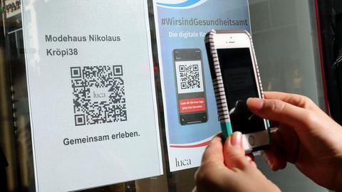Eine Kundin scannt im Modehaus Nikolaus in Rostock den QR-Code der Luca-App zur Kontaktnachverfolgung. (dpa)