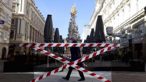 Österreich, Wien: Eine Fußgängerin geht an abgesperrten Bereichen vor Cafés vorbei.  (dpa)