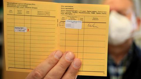 Ein Mitarbeiter eines Altenpflegeheims zeigt seinen Impfausweis mit der Corona-Impfung von Biontech/Pfizer. (dpa)