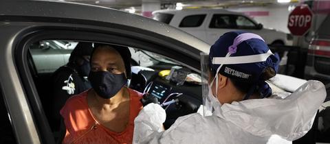 Eine Frau wird in den USA in ihrem Auto gegen Corona geimpft. (AP)