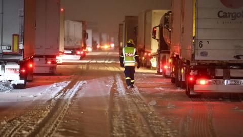 Mitarbieter des Technischen Hilfswerks betreuen Lkw-Fahrer, die auf der Autobahn 4 bei Gera im Stau stehen.  (dpa)