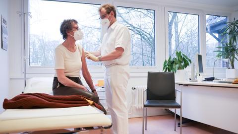 Ein Arzt impft in seiner Praxis eine Patientin gegen das Coronavirus.  (dpa)