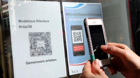 Eine Kundin scannt den QR-Code der Luca-App zur Kontaktnachverfolgung. (dpa)