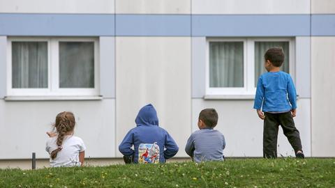 Kinder sitzen auf einer Wiese vor einem Flüchtlingsheim. (dpa)