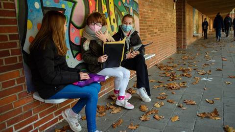 Schülerinnen sitzen auf dem Hof einer Schule (dpa)