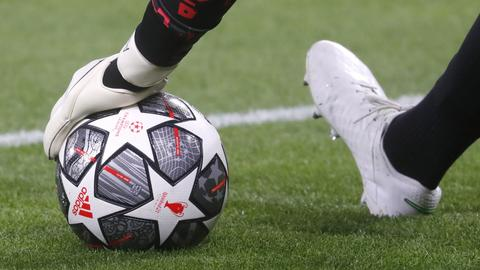 Eine Hand hält einen Fußball auf dem Boden (AP)