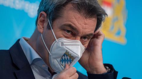 Bayerns Ministerpräsident Söder rückt eine FFP2-Maske mit dem Wappen seines Bundeslandes zurecht. (dpa)