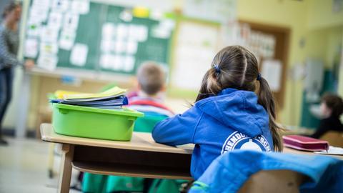 Schülerinnen und Schüler einer Grundschule sitzen mit Abstand in ihrem Klassenraum.  (dpa)