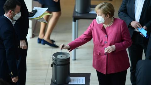 """Bundeskanzlerin Angela merkel wirft ihren Abstimmungszettel während des Votums des Bundestags über die """"Bundesnotbremse"""" in eine Urne ein. (EPA)"""