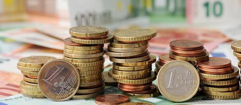 Stapel von Münzen liegen auf Euro-Geldscheinen (dpa)
