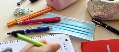 In einer Schule liegt während einer Unterrichtsstunde ein Mund-Nasen-Schutz auf dem Tisch einer Schülerin. (dpa)