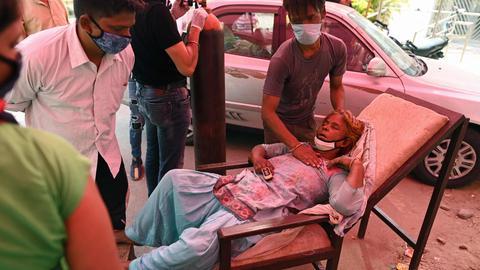 Eine Corona-Infizierte mit Atemproblemen liegt auf einem Stuhl (in Ghaziabad, Indien) (AFP)