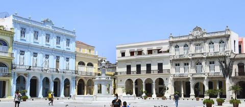 Menschen gehen mit Mund-Nasen-Schutz über einen Platz in Havanna (Archivbild). ()