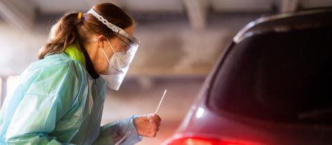 """Eine Helferin testet Insassen eines Autos im """"Testzentrum am Zoo"""" in Hannover mit einem Schnelltest auf das Coronavirus. ()"""