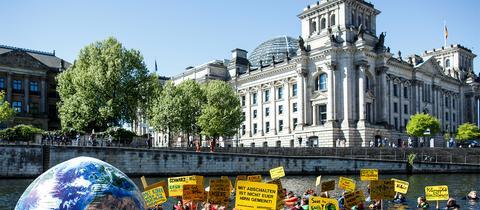 Aktivisten der Umweltschutzorganisation Greenpeace schwimmen am Reichstag in der Spree in Berlin. Mit der Aktion will die Organisation für mehr Klimaschutz demonstrieren. (dpa)