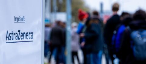 Ein Schild vor einem Impfzentrum in Schwerin zeigt, dass dort mit AstraZeneca gegen das Coronavirus geimpft wird. Menschen stehen Schlange für eine Impfung. (dpa)