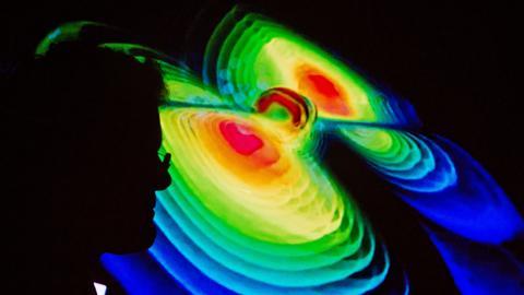 Der Schattenriss eines Wissenschaftlers ist am 11.02.2016 auf einer Visualisierung von Gravitationswellen während einer Pressekonferenz vom Max-Planck-Institut für Gravitationsphysik (Albert Einstein Institut) in der Leibniz Universität in Hannover zu sehen.