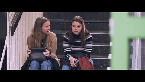 Zwei Schülerinnen sitzen auf Treppe