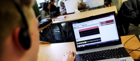 Schüler produzieren am Laptop einen Radiobeitrag