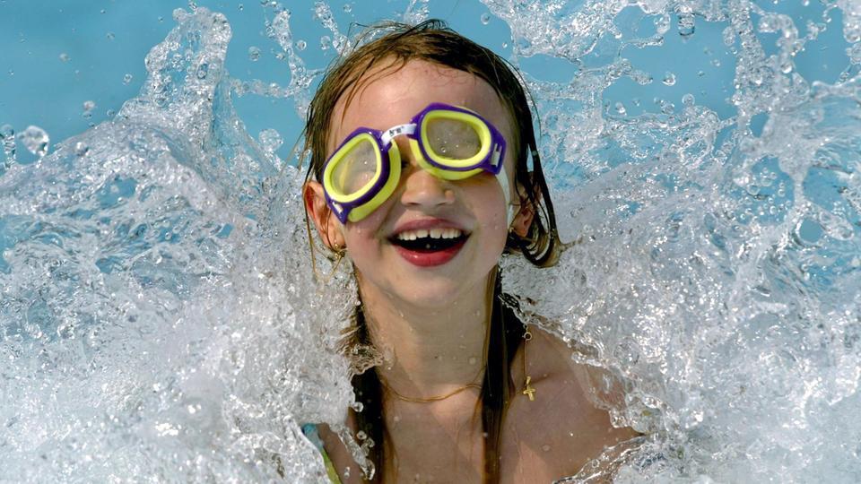 Der sechsjährigen Laura ist vor lauter Begeisterung über die Wellen im Essener Gruga-Freibad die Schwimmbrille verrutscht.