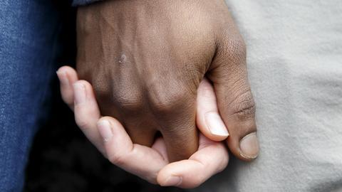 Zwei Menschen halten sich am 25.11.2017 in Genf (Schweiz) bei einer Demonstration gegen mutmaßliche Sklavenauktionen in Libyen an den Händen