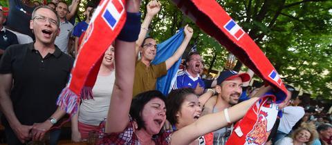 Französische Fans singen am 07.07.2016 in München (Bayern) in einem Biergarten bei der Übertragung des Halbfinales der Fußball-Europameisterschaft zwischen Deutschland und Frankreich die Nationalhymne.