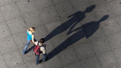 Ein Paar hält sich beim Spazierengehen an den Händen und wirft dabei lange Schatten