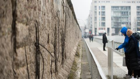 Touristen betrachten  an einem Stück der ehemaligen Berliner Mauer eine Informationstafel.