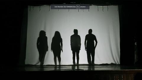 Menschen auf Bühne im Schattenriss