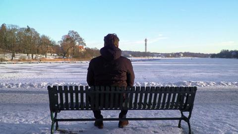 Mann sitzt auf Bank im Schnee