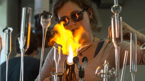 Frau bearbeitet Glas mit einem Bunsenbrenner