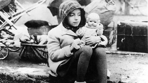 Ein Mädchen aus einem Flüchtlingstreck mit ihrer Puppe im Arm in den Wirren der Nachkriegszeit.