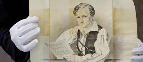 Mann hält Bleistiftzeichnung - Porträt - in der Hand