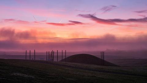 Die Sonne geht hinter dem rekonstruierten gewaltigen Grabhügel vor dem Museum Keltenwelt in Glauburg auf.