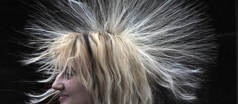 """Frau testet in der Experimentalausstellung """"Physik im Kaufpark"""" die elektrostatische Aufladung an ihren Haaren."""